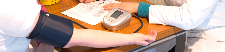 Es zeigt eine Person beim Blutdruckmessen.