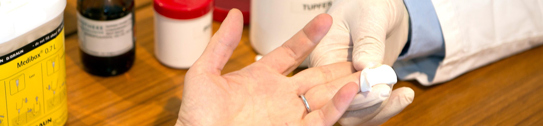 Es zeigt wie einer Person ein Tropfen Blut aus den Finger abgenommen wird.